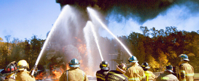 Picture of Fire School students using hoses to put out fires in training